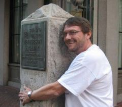 Jefferson Highway President Mike Conlin hugs JH Marker in New Orleans.