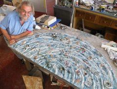 Artist Erik creating mosaic for drain.