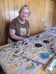 Volunteer creating mosaic.
