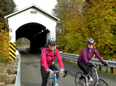Bicyclists Riding Past A Covered Bridge